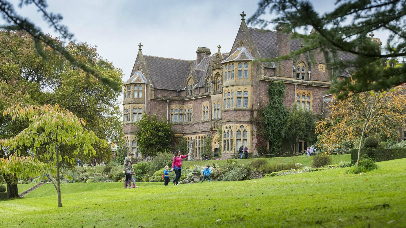A family walking across the south garden in front of the house at Knightshayes on an autumn day