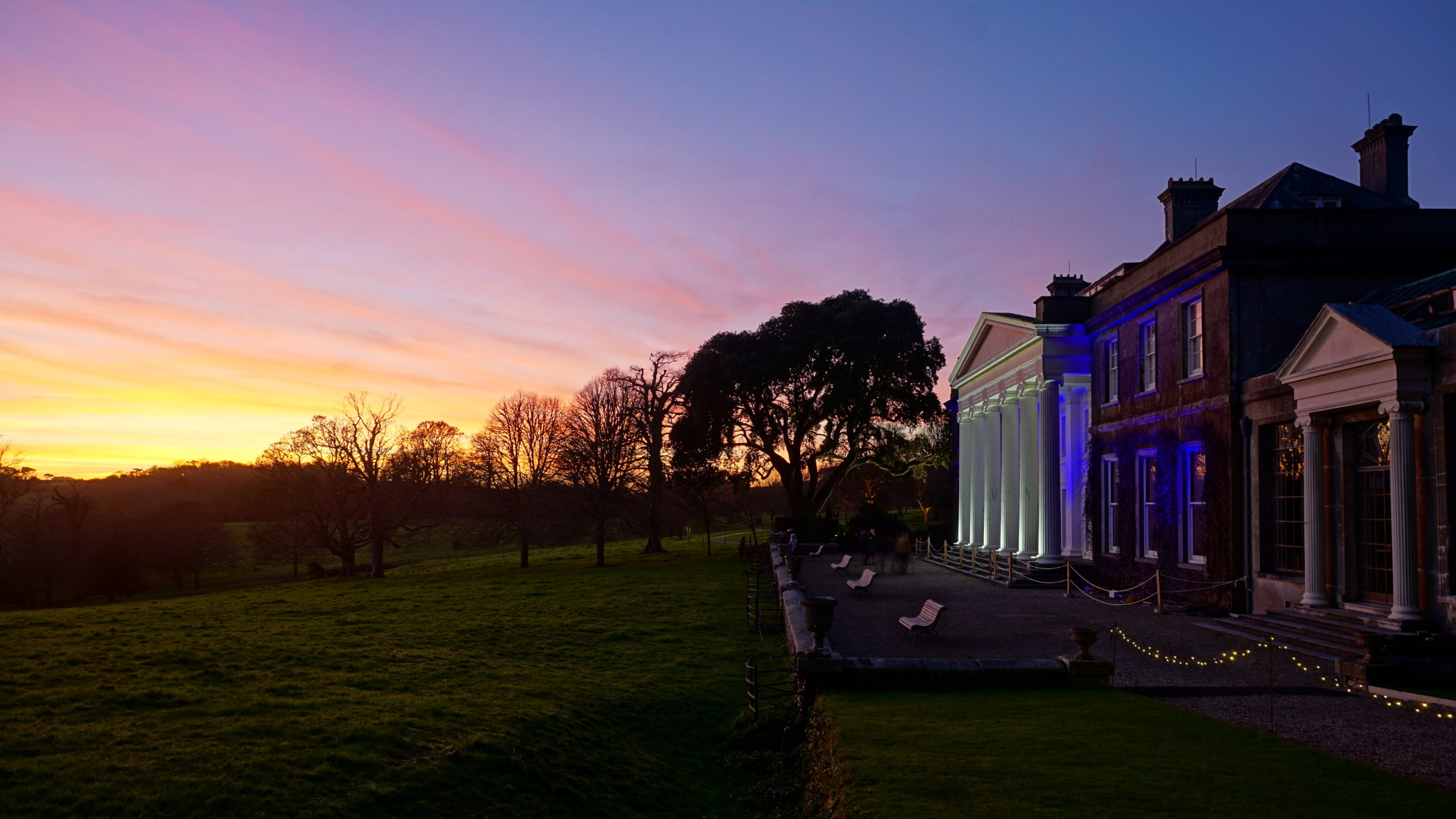 The sun sets on the illuminated Trelissick house at Christmas