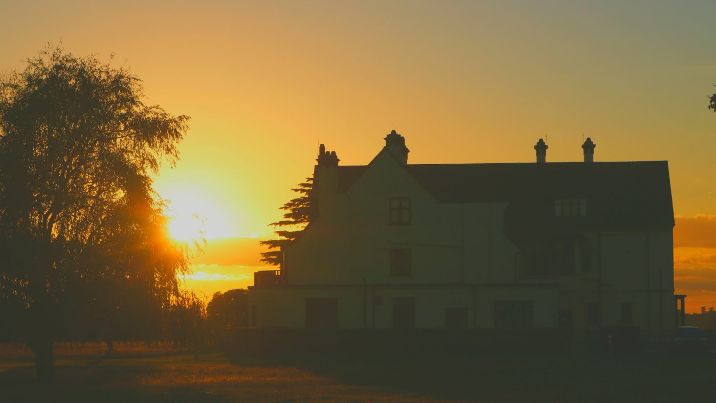 Sun sets behind Tranmer House at Sutton Hoo