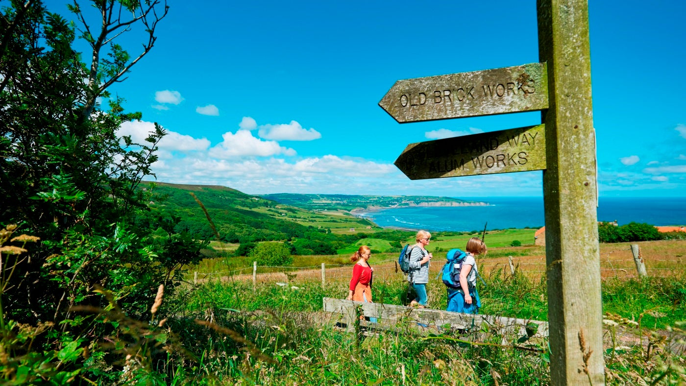 A group walks in the sunshine at Ravenscar with countryside and blue sea in the background