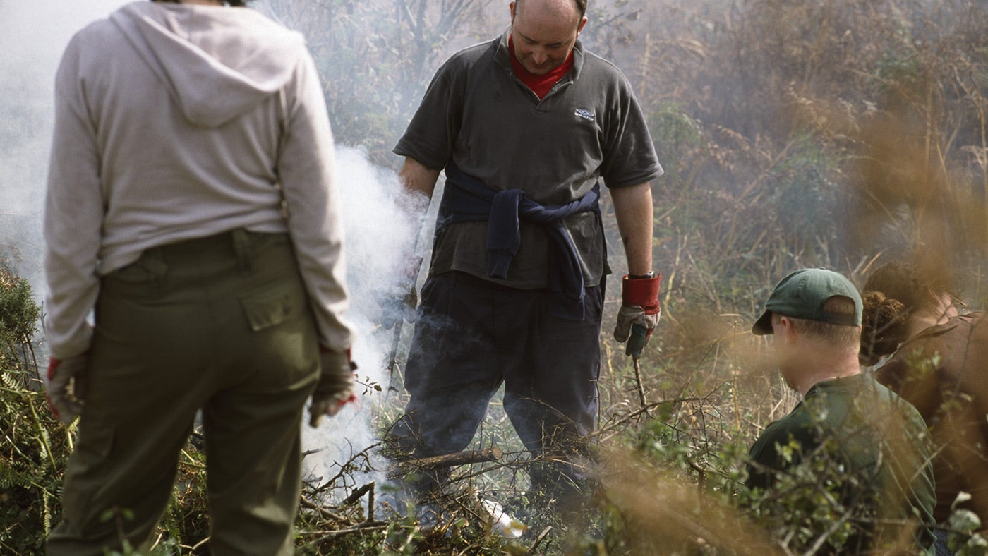 Volunteers burning vegetation on a working holiday