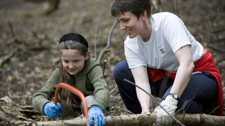 Family learning about woodland conservation on a working holiday