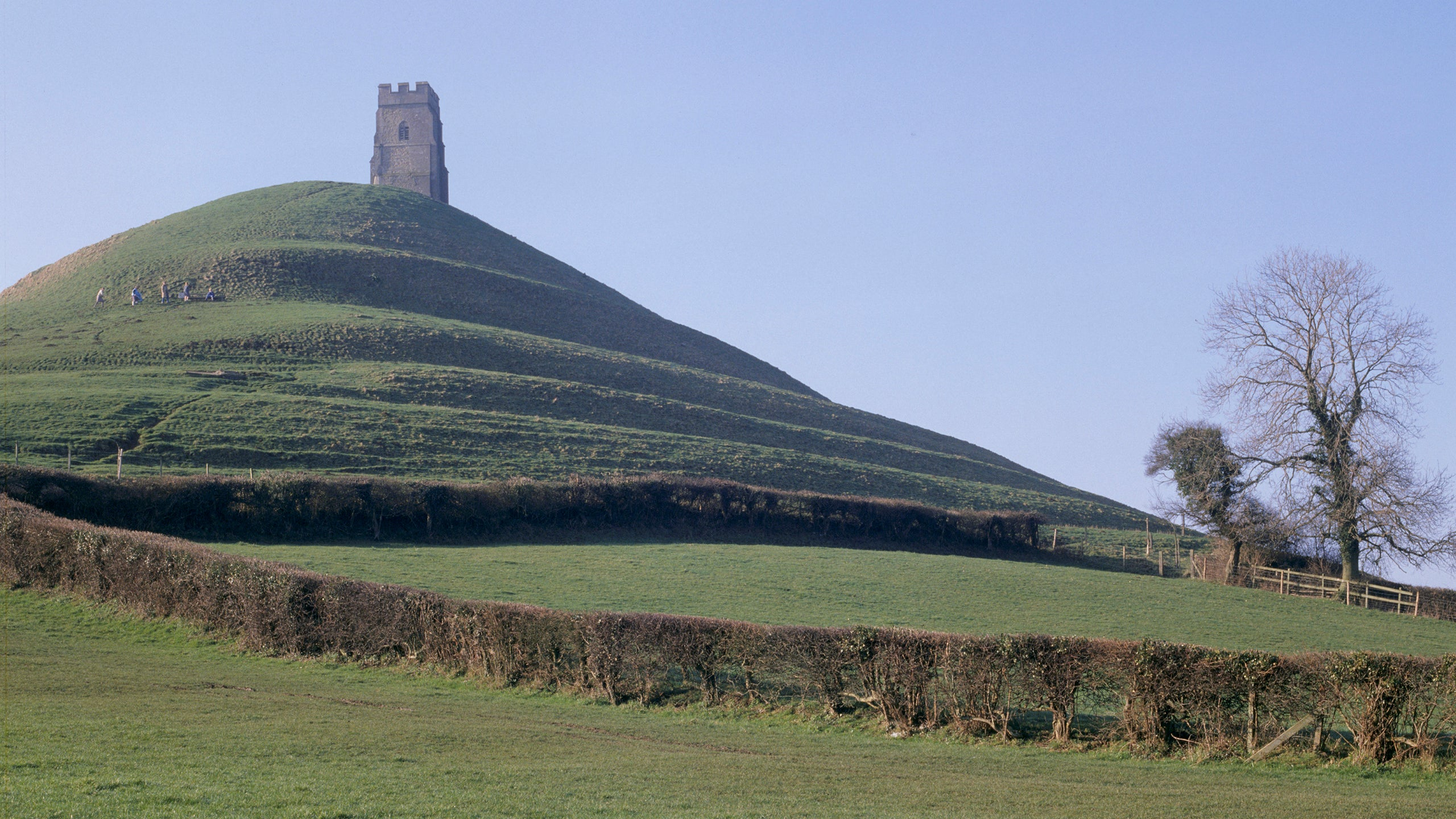 A view across a field to Glastonbury Tor, Somerset, with the remains of the 15th century tower at the summit