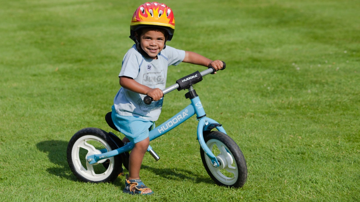 A young child rides a bike across grass on a sunny day