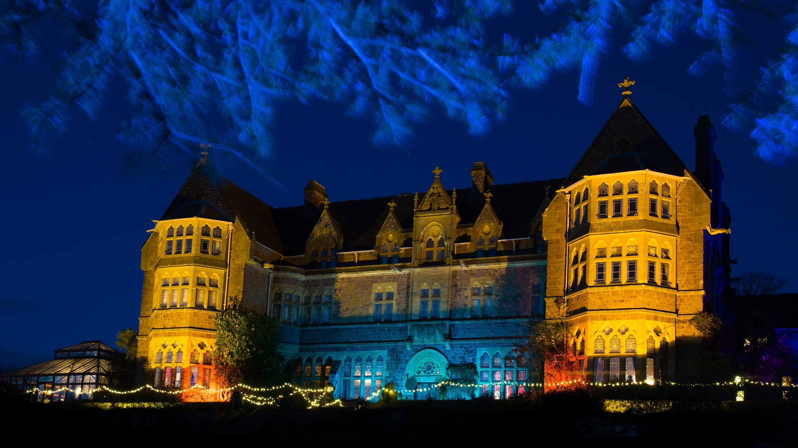 The gardens and house illuminated with lights for Christmas at Knighthayes