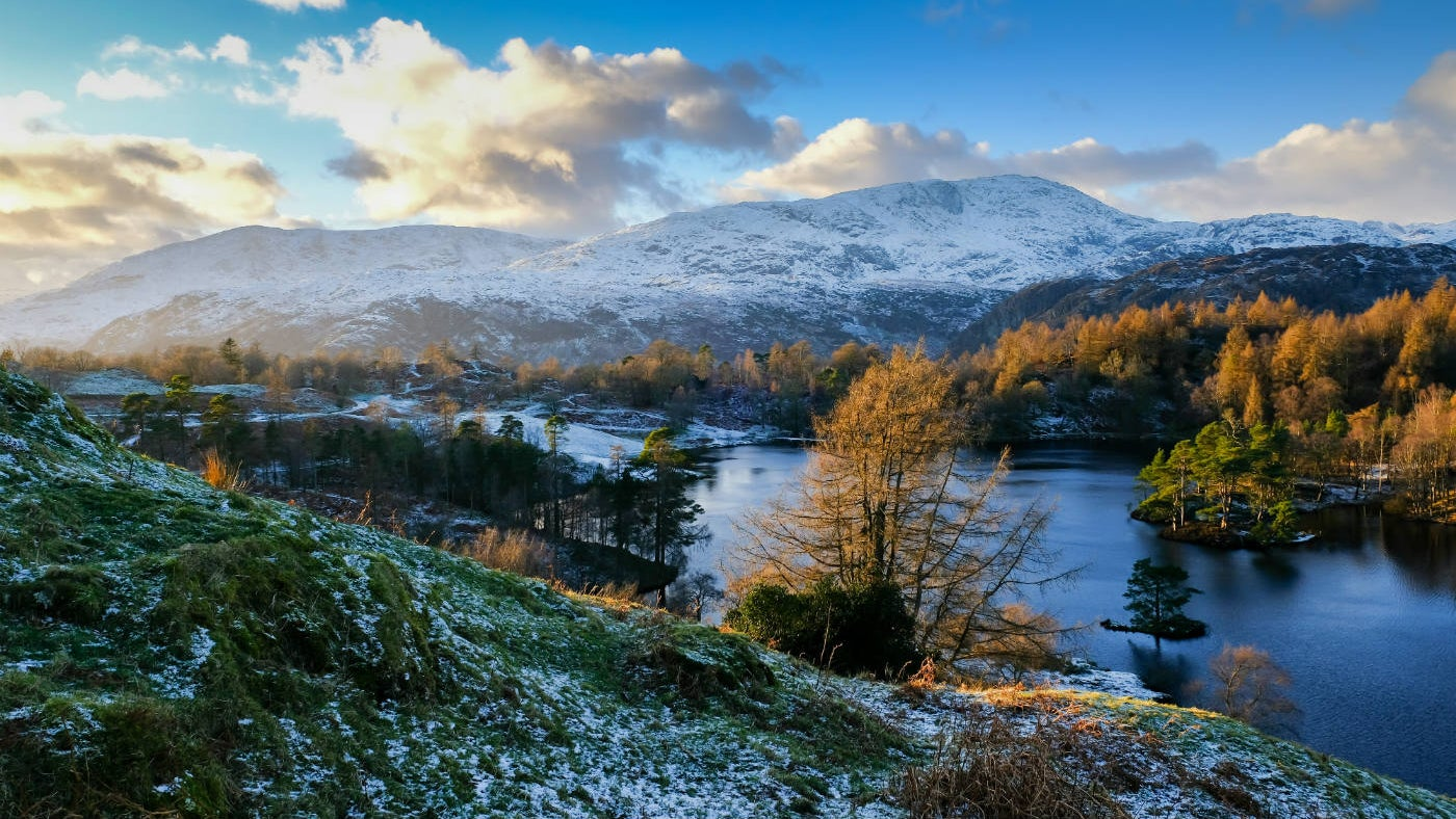 Tarn Hows in winter, showing the Old Man of Coniston dusted in snow