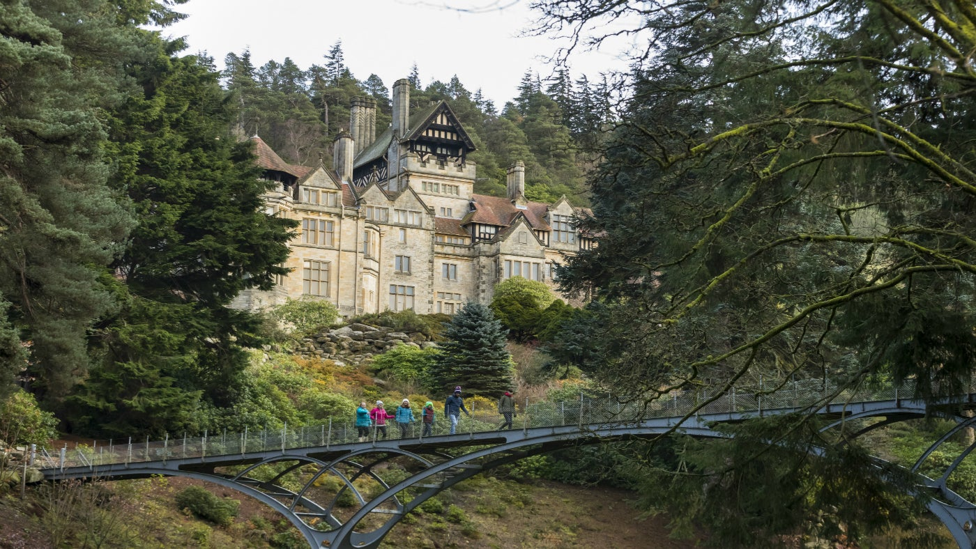 A family walks across the iron bridge at Cragside, with the house in the background