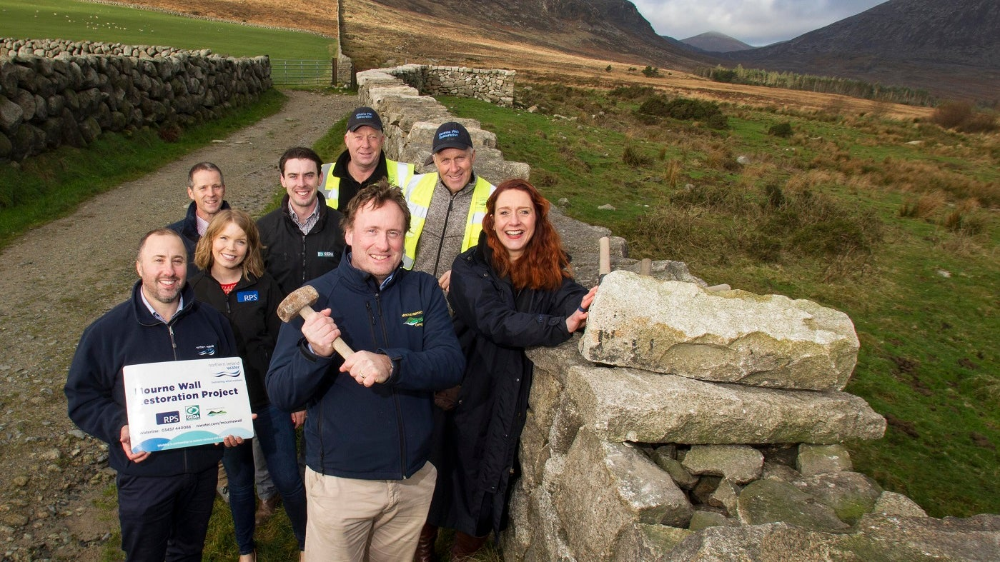 Members of the project team put on the last capping stone to mark the completion of the Mourne Wall Restoration Project