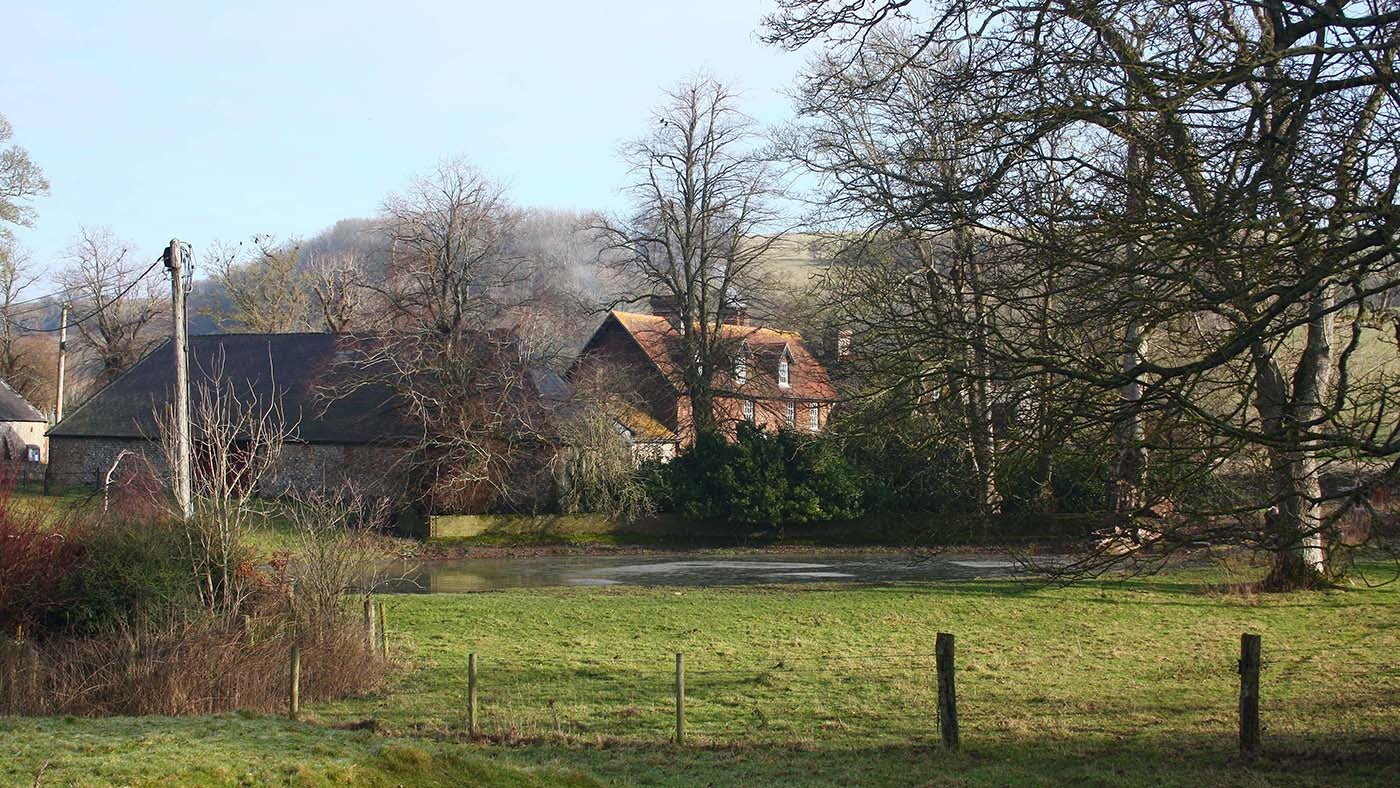 Saddlescombe farmhouse and pond in winter