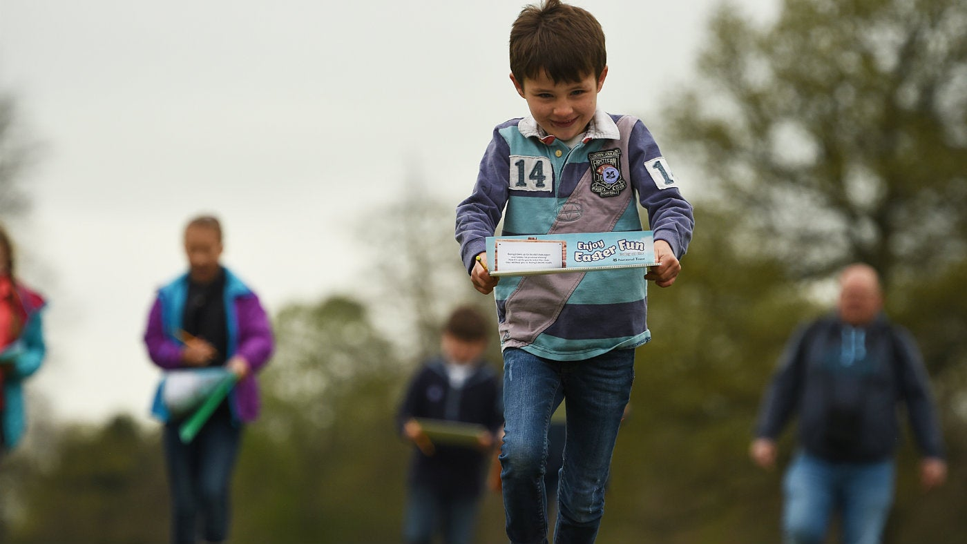 A child races to complete an Easter egg hunt at a National Trust property
