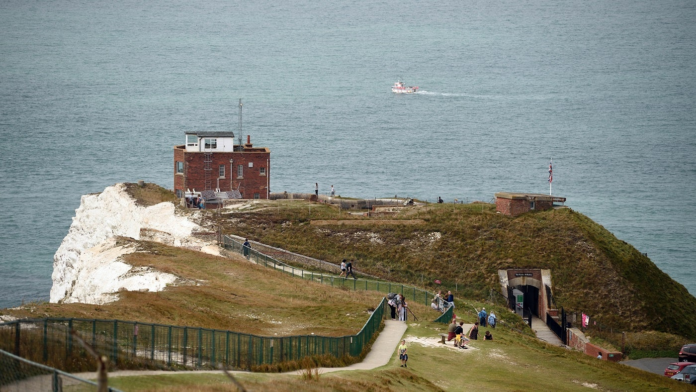 The Needles Battery entrance arch and signal station viewed from higher up on the downs and surrounded by sea
