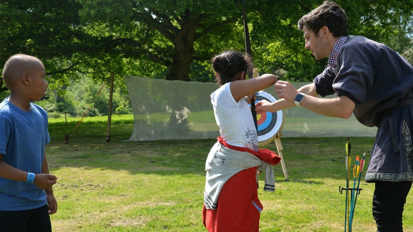 Children enjoying archery tuition at Bodiam Castle in East Sussex