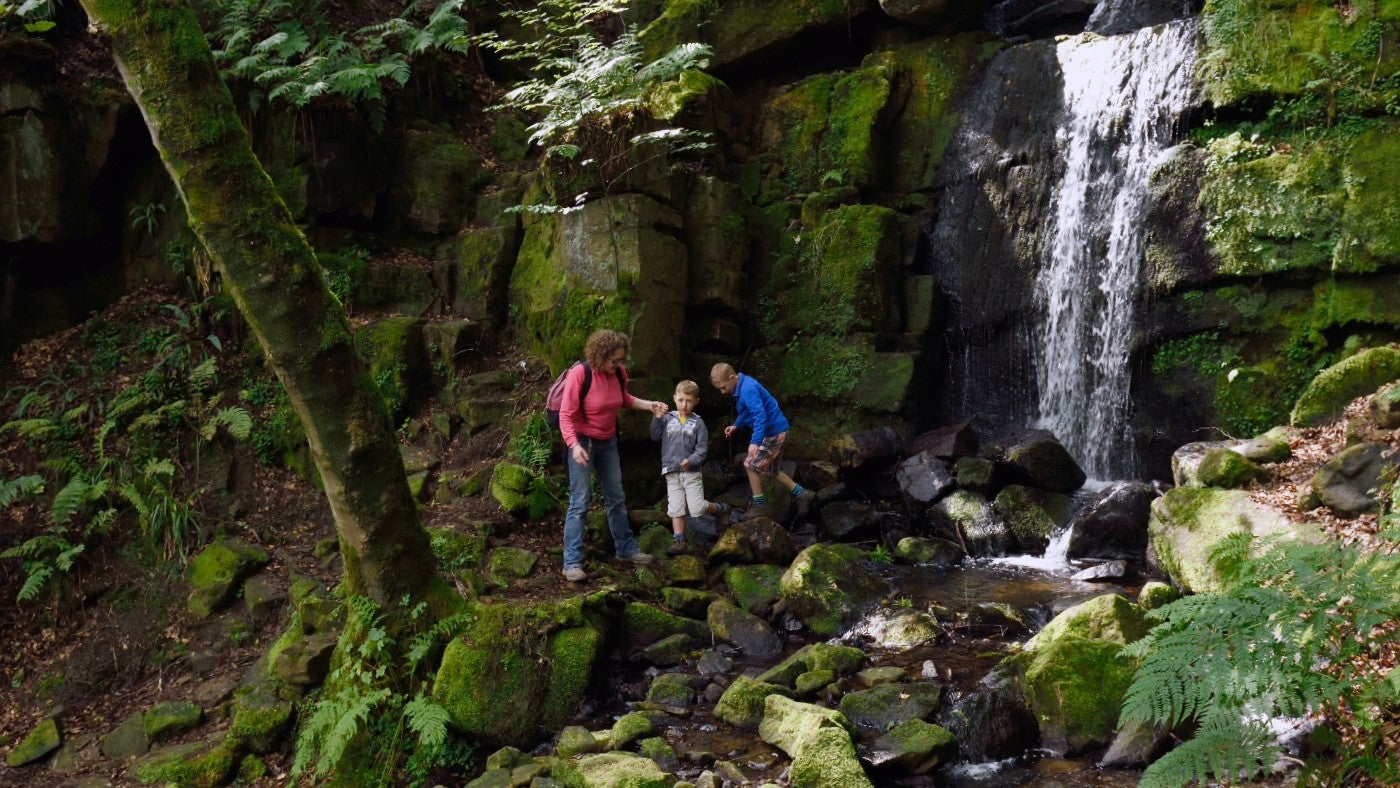 Visitors near a waterfall at Hardcastle Crags, West Yorkshire.