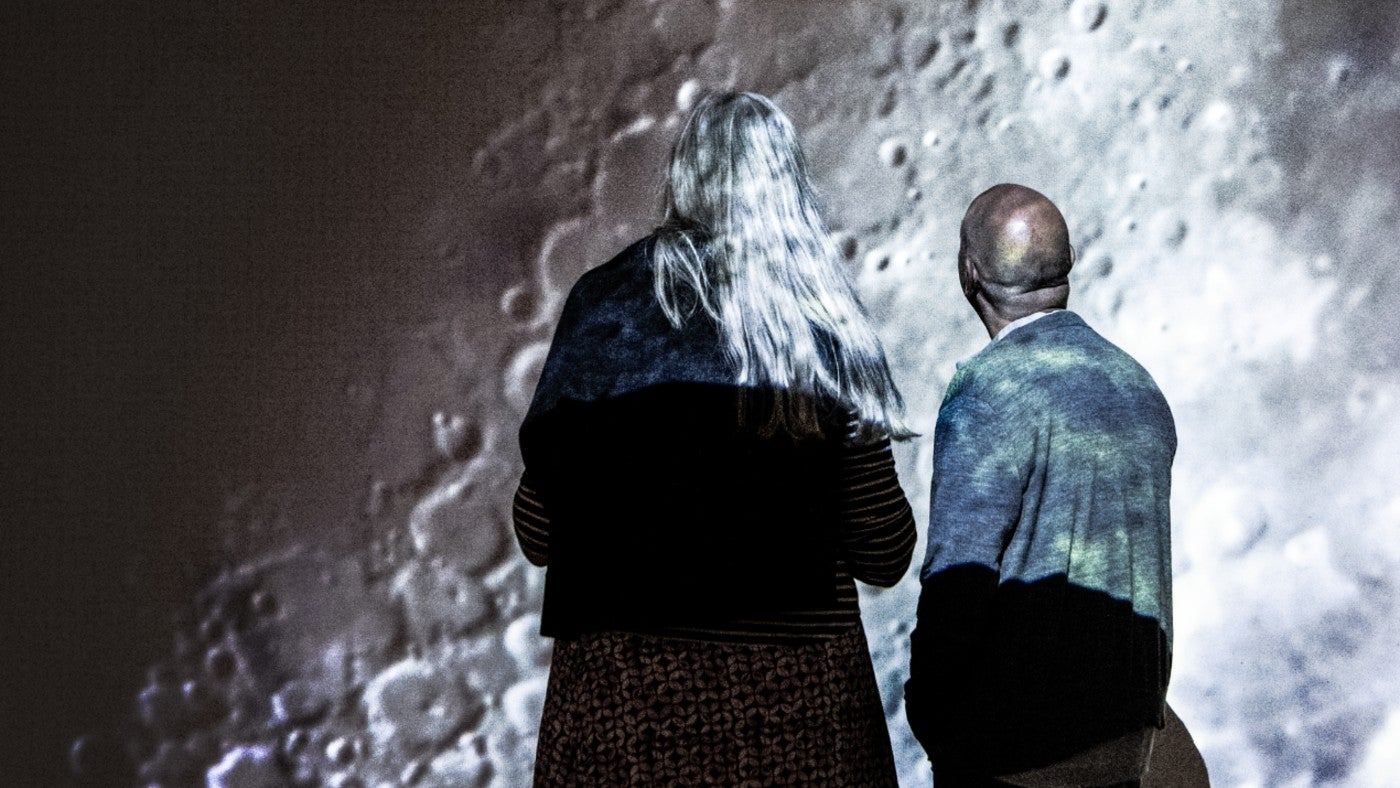 Artists Neville and Joan Gabie looking at a film of the moon