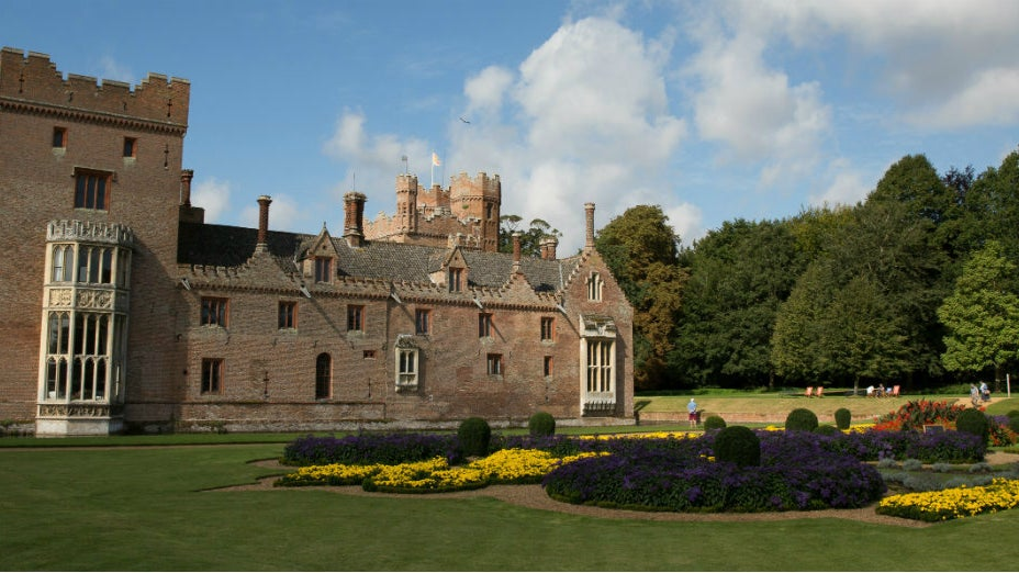 Oxburgh Hall in the summer sunshine from across the blooming French Parterre