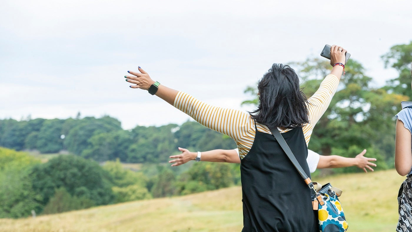 A women with her back to the camera stands with raised arms looking out over Lyme's parkland