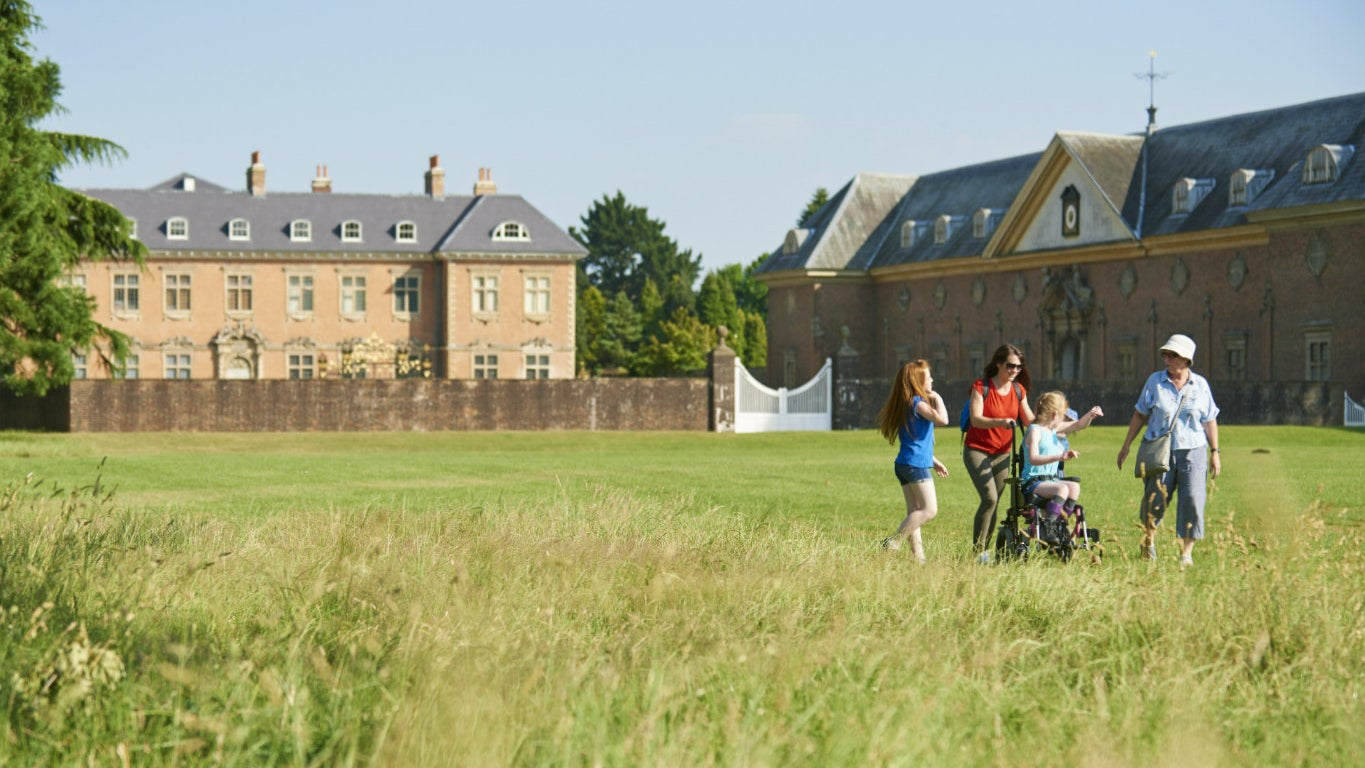 A family walks through the long grass in the park at Tredegar House