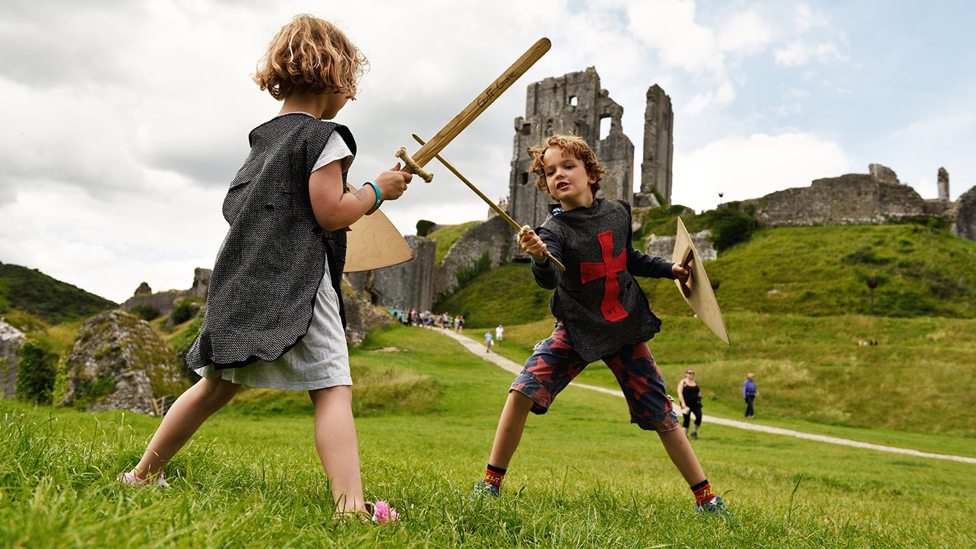 Two children playing with toy swords at Corfe Castle