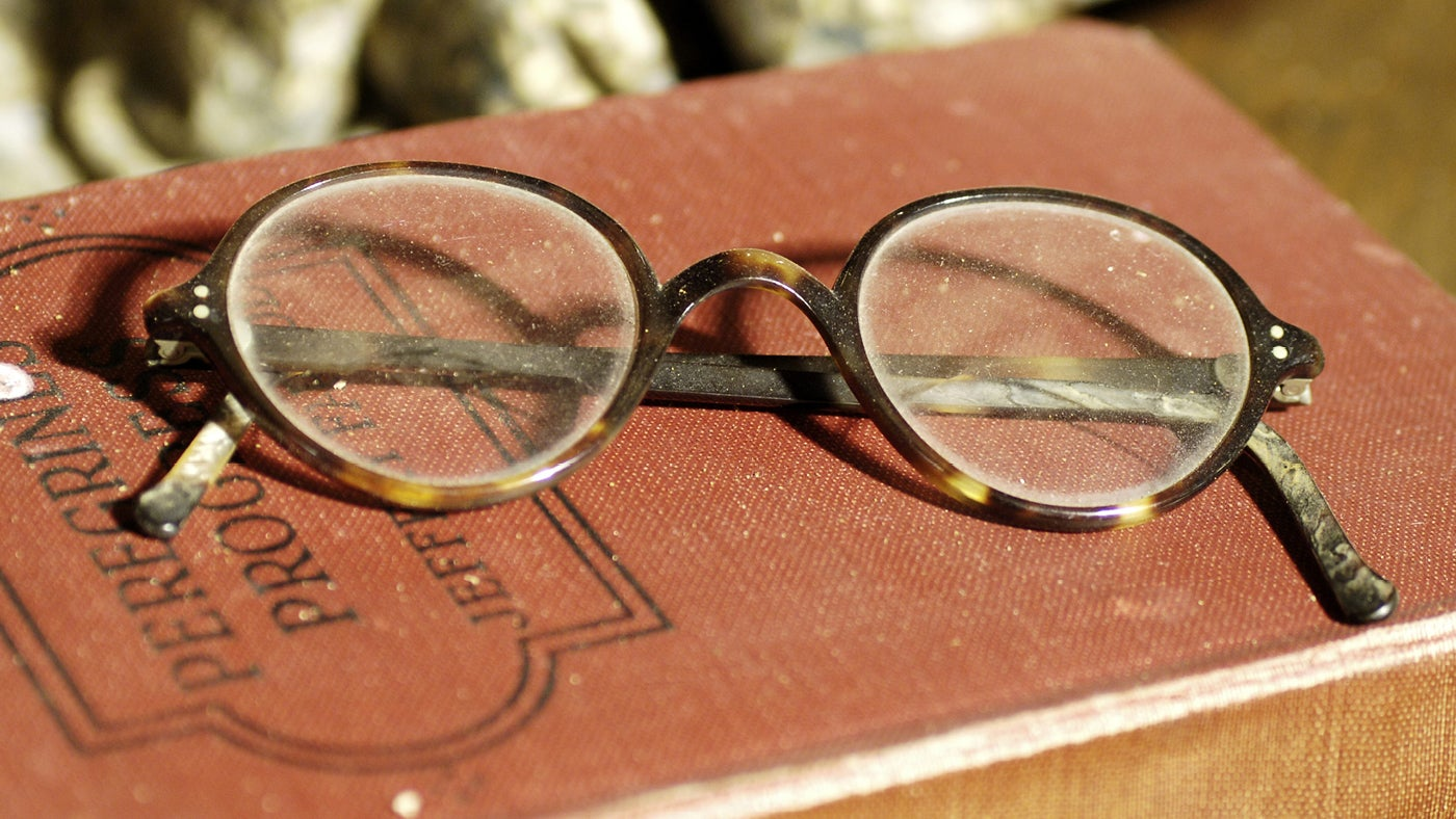 Charles Wade's spectacles resting on a book, part of the collection in the Living Room at the Priest's House at Snowshill Manor, Gloucestershire
