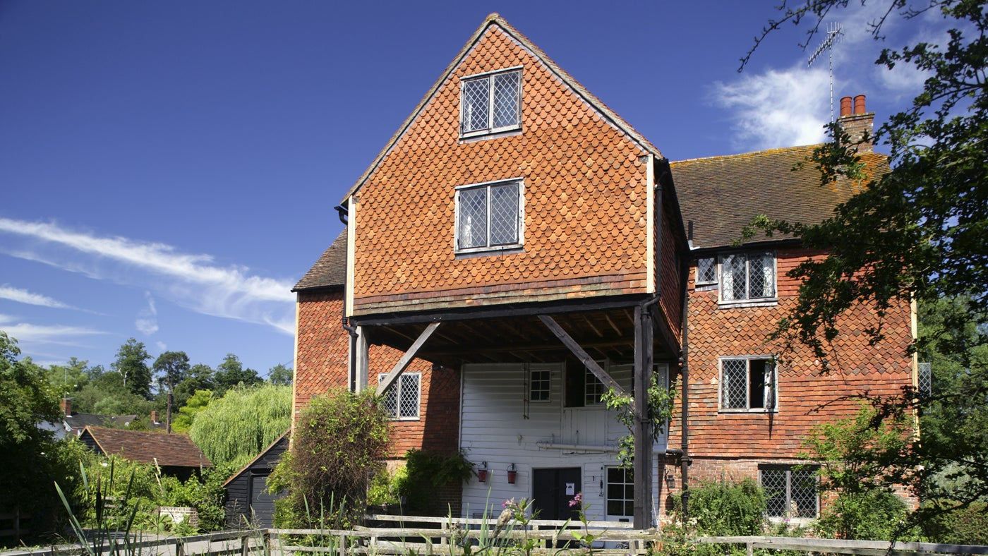The exterior of the mill sitting astride the Tillingbourne river