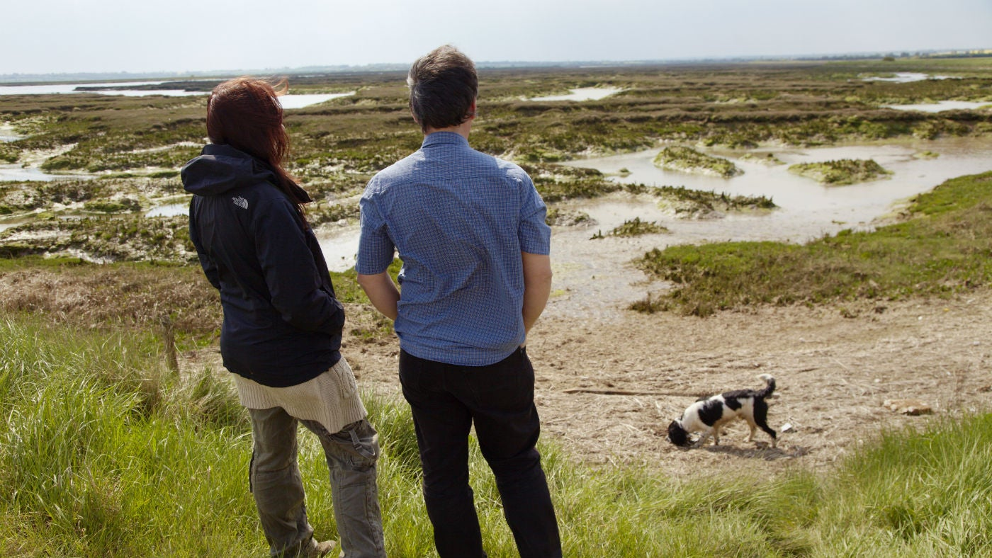 Couple with a black and white spaniel look out across the grey, green and brown salt marsh