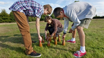 Boys setting up skittles in the meadow at Emmetts Garden, Kent