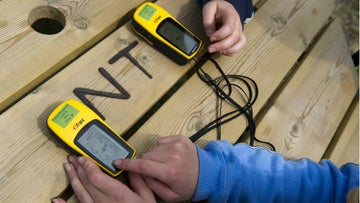 Two GPS devices on table used for geocaching