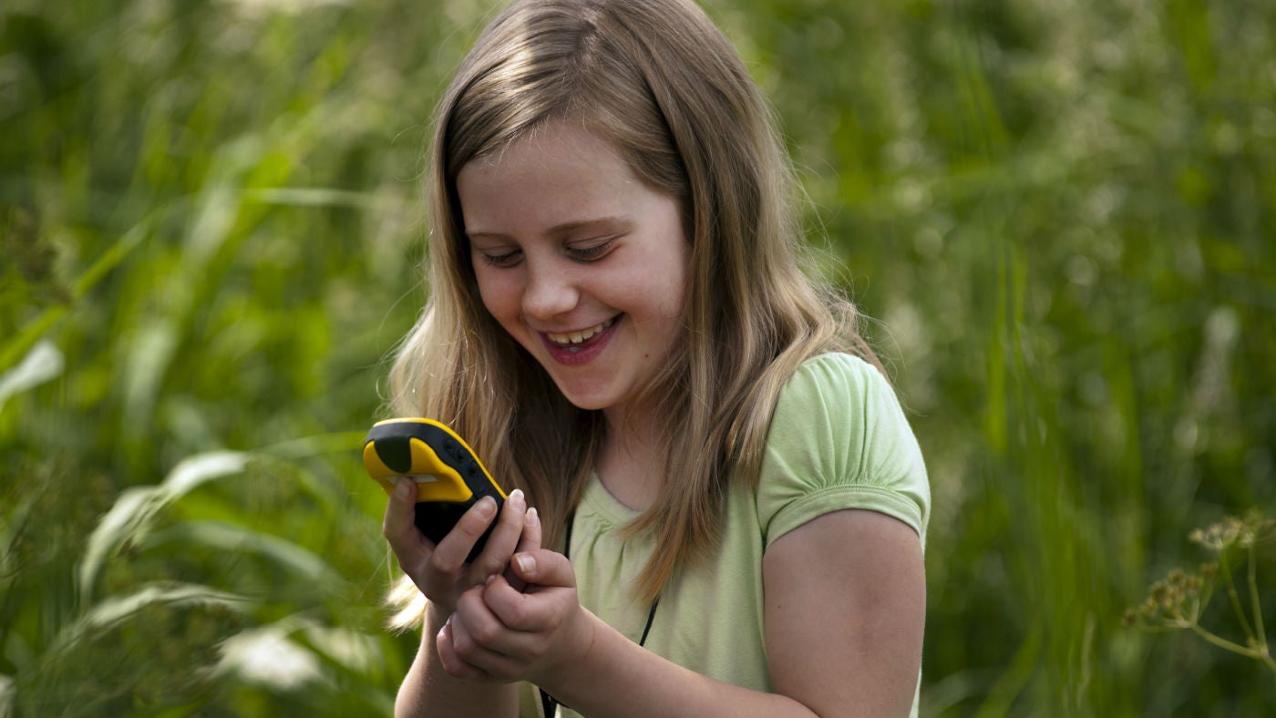 Child with black and yellow handheld GPS unit