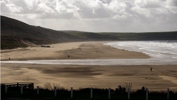 Visitors on the beach at Woolacombe looking towards the headland of Baggy Point