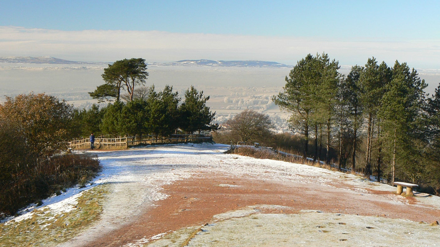 A snowy hill top looking out at a snow covered landscaped and snow-capped hills