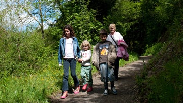 Family walk the woodland path at Dolaucothi