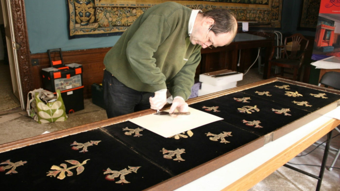 Conservator undertaking work on the Mary, Queen of Scots bed hanging