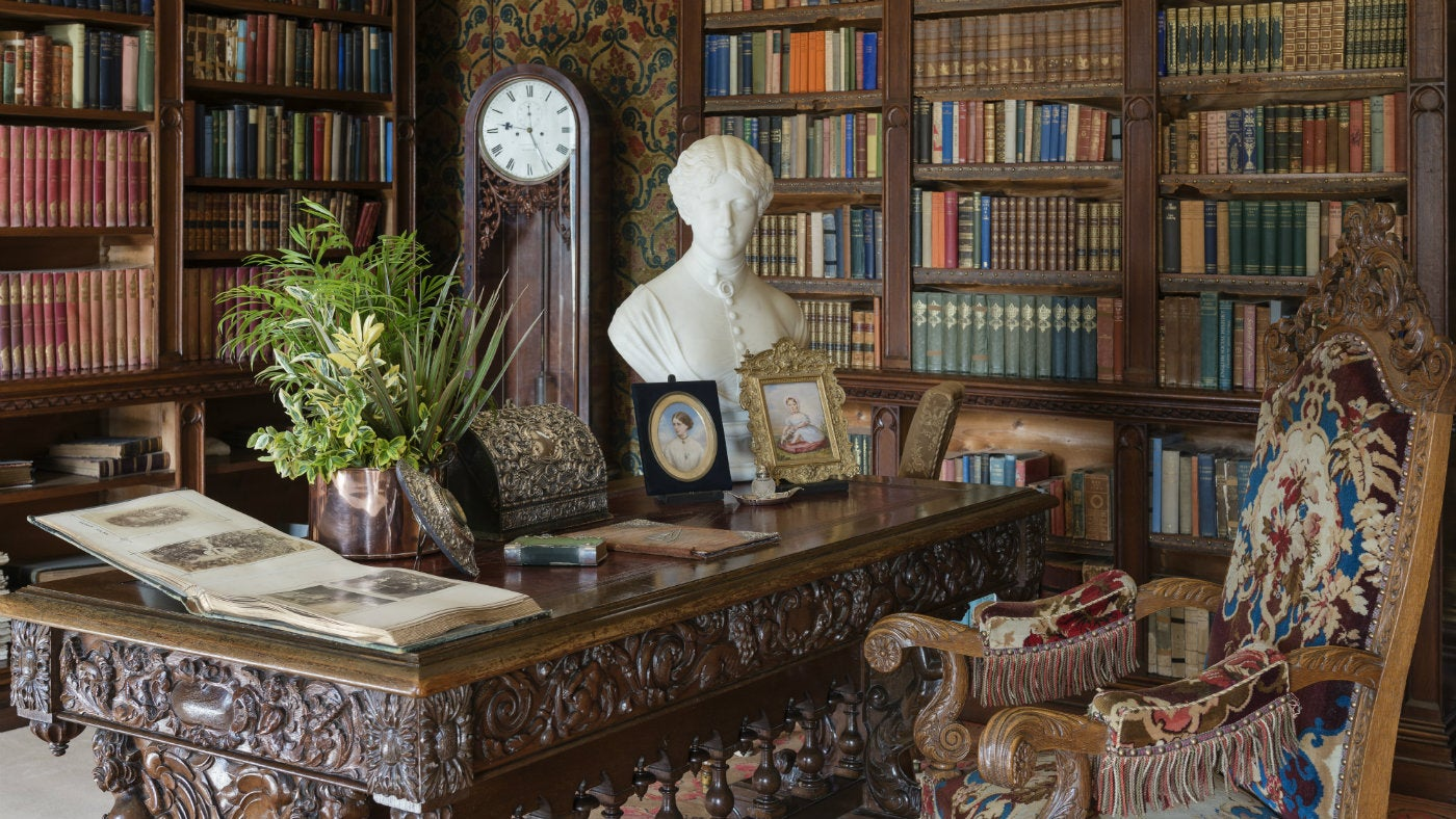 Bookshelves, a richly carved table, a longcase clock and a marble bust in a corner of the Library at Oxburgh Hall, Norfolk