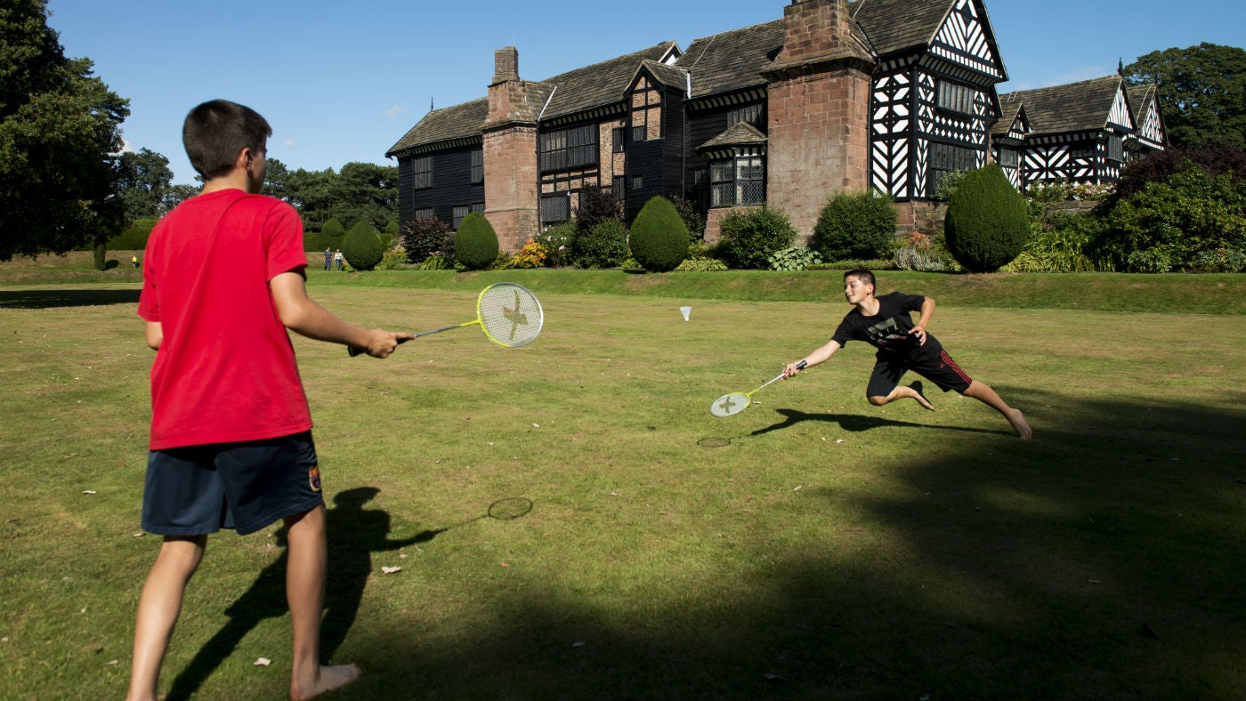 Children play badminton in the Moat Garden at Speke Hall