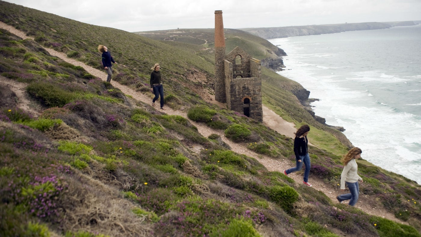 Visitors walking on the coast path above Towanroath Shaft pumping engine house, part of the Wheal Coates mine, near St Agnes, Cornwall