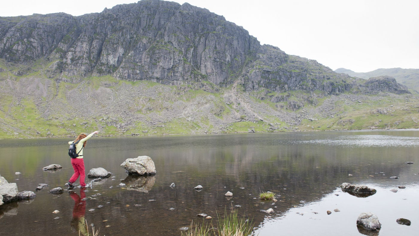 A woman stepping on stones at Stickle Tarn