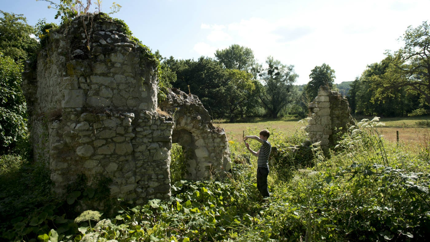 Visitor admiring the ruins of St Mary's Priory at Ankerwycke, Surrey