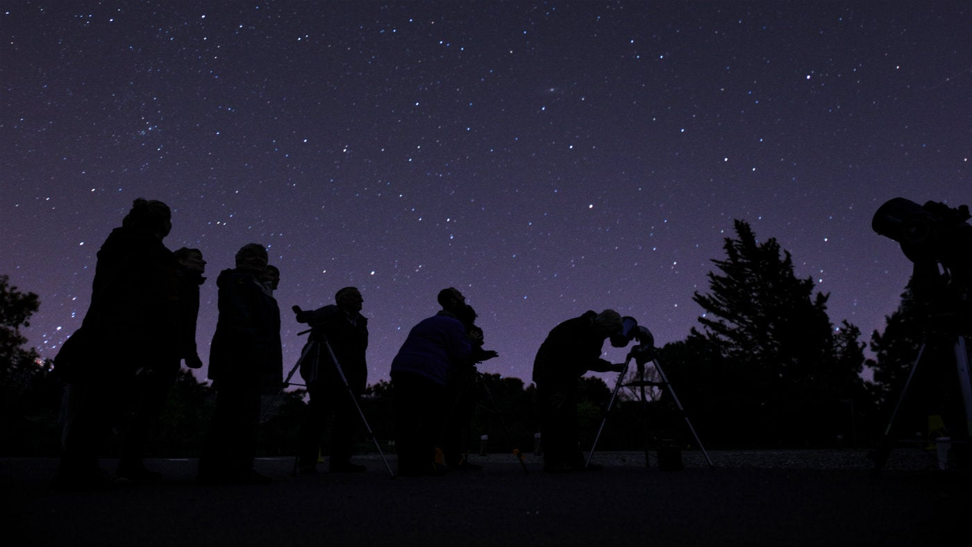 Visitors looking up at the starry night sky