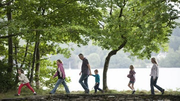 Family walking near Wray Castle on the west shore of Windermere, Cumbria.