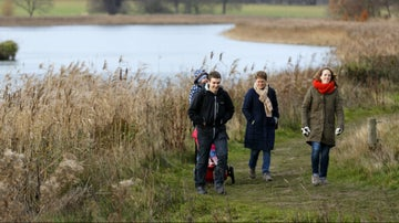 A group walking in winter around the lake at Blickling